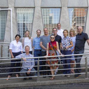 groepsfoto met gevel amerikaanse ambassade